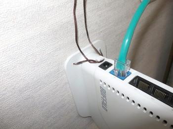 無線LANルータの本体にあるフックに針金を巻き付けて固定する